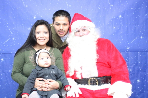 Teen parents Guadalupe and Edwin have their family photo taken with Santa.